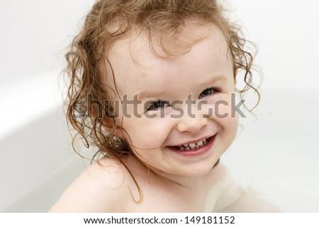 Baby having fun in bath - stock photo