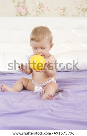 Baby having fun playing with a ball sitting on a bed