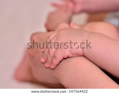 Baby hold mother's hand - stock photo