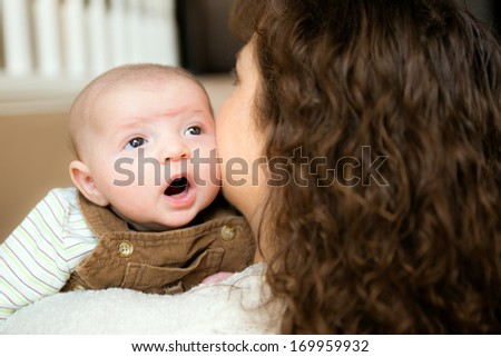 Baby holding his head up for first time while being held by mother - stock photo