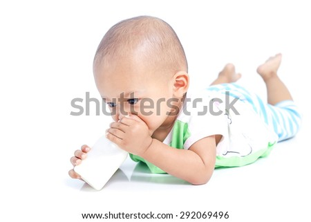 baby holding milk bottle and drinking - stock photo