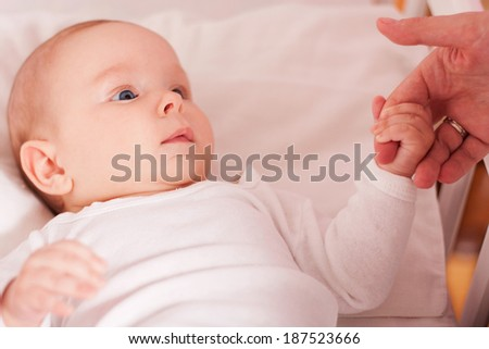Baby holding mother's hand and looking in her eyes - stock photo