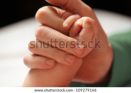 Baby holding mother's hand. Shallow DOF, focus on baby hand.