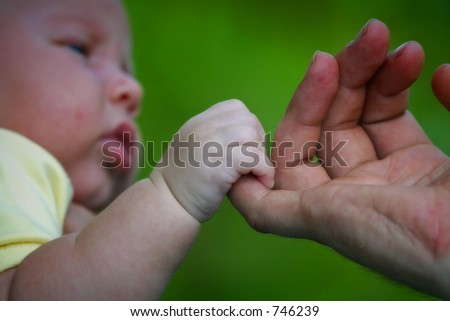 baby holding onto parents hand - stock photo
