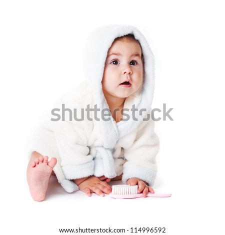 Baby in a bathrobe after bath with comb