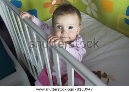 Baby  in a Crib - sitting and watching to camera - stock photo
