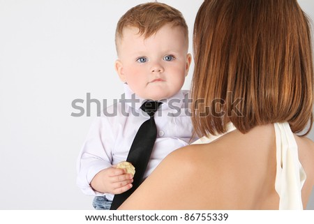 baby in a shirt and tie with his mother - stock photo