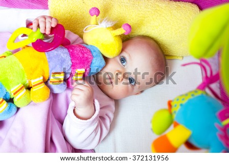 baby in bed with a colorful toy - stock photo