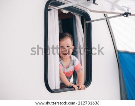 baby in camper window - stock photo