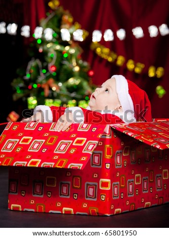 Baby in Christmas costume sitting in a large present box and looking up - stock photo