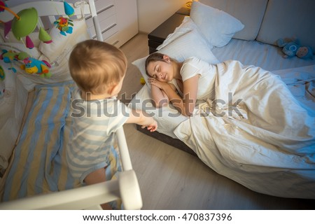 Baby in cot crying and trying to wake up mother that fell asleep