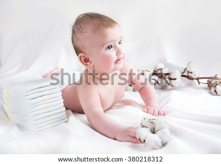 Baby in diaper on a white background with a branch of cotton - stock photo