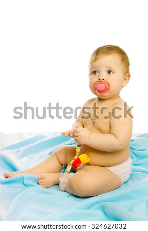 baby in diapers with a pacifier sitting on the floor - stock photo
