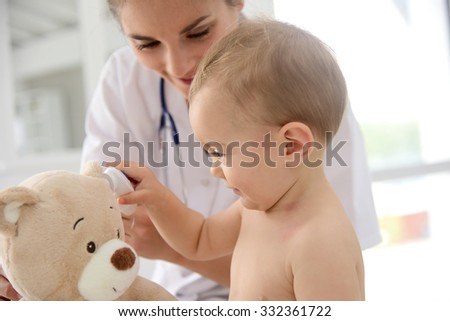 Baby in doctor's office playing with stethoscope and teddy bear - stock photo