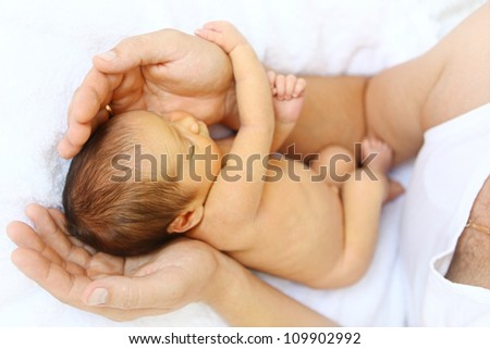 Baby in father's hands - stock photo