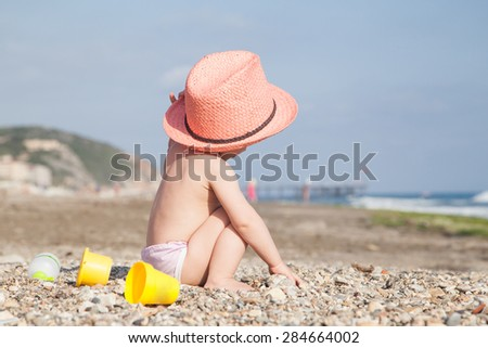 Baby in hat playing on the beach - stock photo