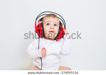 Baby in headphones listening to music - stock photo