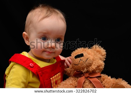 Baby in overalls with a puzzled expression - stock photo