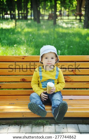 baby in panama sitting on a bench eating ice cream - stock photo
