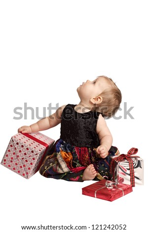 Baby in patchwork dress holds gifts and looks up - stock photo