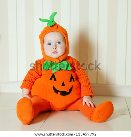Baby in pumpkin suit on Halloween eve - stock photo