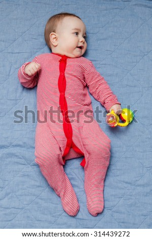 Baby in red and white striped bodysuit lying on the blue blanket holding rattle toy. Baby looking sideways. Selective focus on baby head. - stock photo