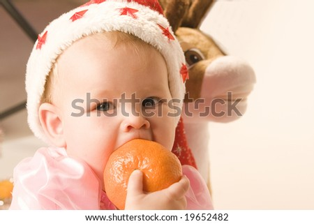 Baby in red christmas hat with tangerine in her mouth on white ground