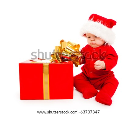 Baby in red clothing and Santa hat busy packing Christmas present - stock photo