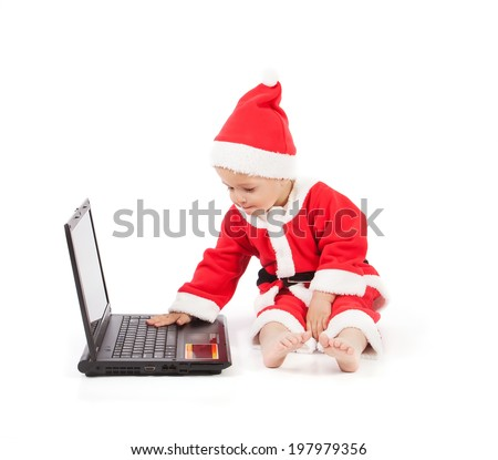 Baby in santa clothes with laptop on the white background - stock photo
