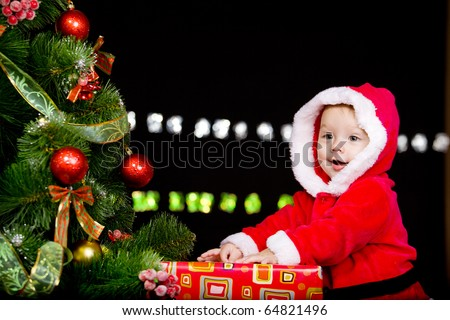 Baby in Santa costume on the black background - stock photo