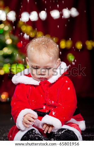 Baby in Santa costume playing with the snow falling - stock photo