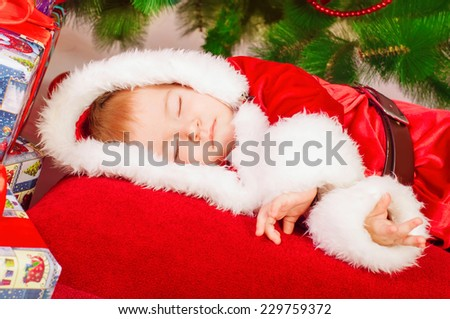 baby in Santa costume sleeping at the Christmas tree with gifts - stock photo