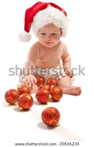 Baby in Santa hat playing with Christmas balls, isolated - stock photo