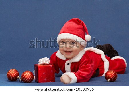 baby in santa's suit with gift and christmas balls - stock photo