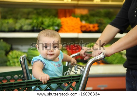 Baby in shopping cart - stock photo