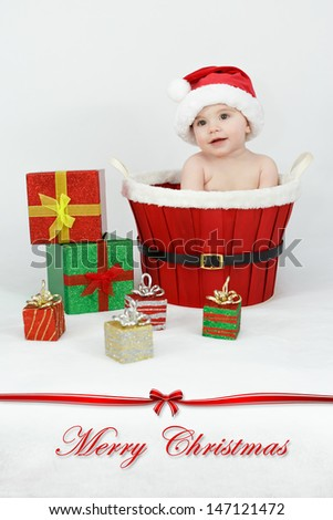 Baby in the basket with Christmas gifts - stock photo