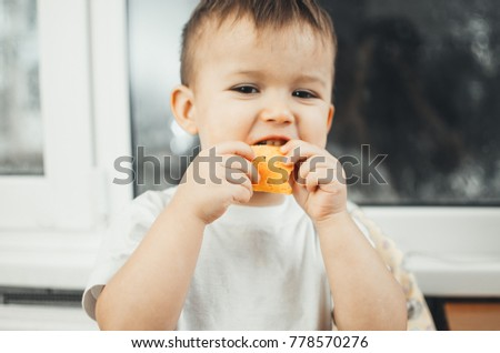 baby in the kitchen in a white shirt eating cheese