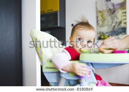 Baby in toddler seat - eating; eyes wide open - stock photo