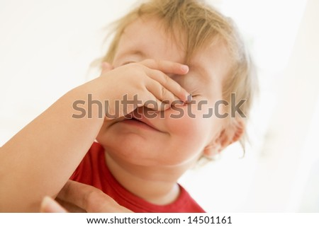 Baby indoors putting hand over face - stock photo
