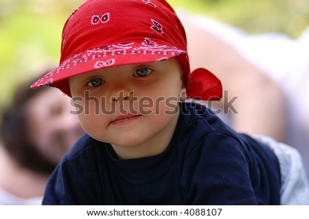 Baby infant with big blue eyes in red hat
