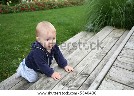 baby is crawling and climbing the stairs outside - stock photo