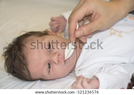 Baby is drinking medicine syrup