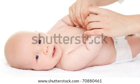 baby is enjoying massage from mother