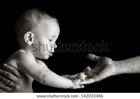 Baby is holding father's hand. Black and white photo. - stock photo