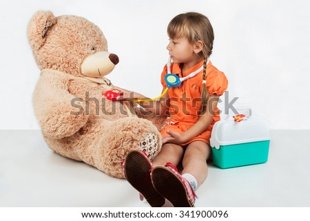 Baby is playing doctor, treats a bear, on white background - stock photo