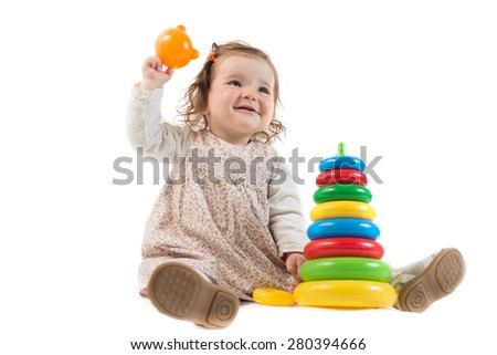 Baby is playing with colored toy pyramid over the white background - stock photo