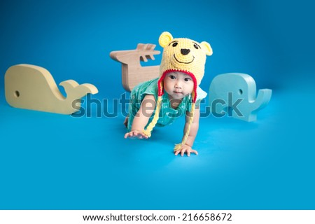 baby is playing with toys over blue background - stock photo