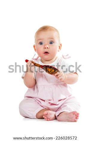 Baby is sitting, looking at the camera and holds in hands wooden spoon isolated on white background - stock photo