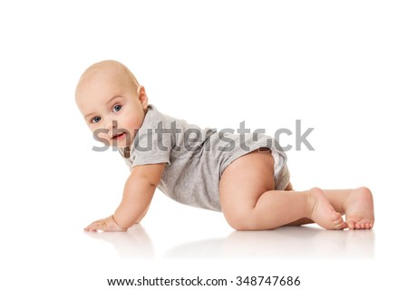 Baby is sitting on floor, isolated on white