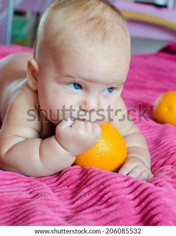 Baby is trying to taste orange - stock photo